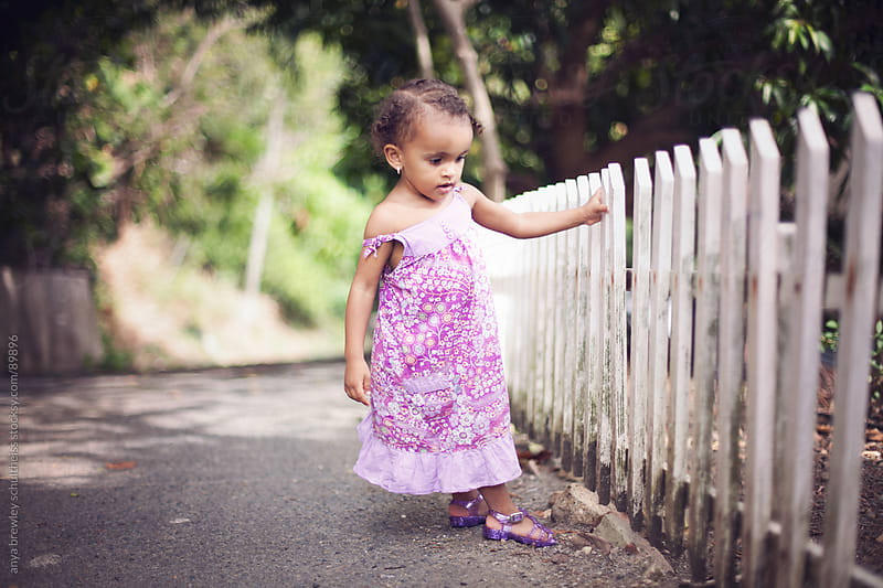 Young girl standing at a old white picket fence by anya brewley schultheiss for Stocksy United