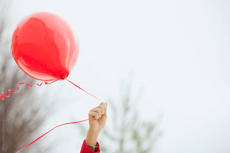 Valentine's: Hand Holding Balloon Against Sky by Sean Locke for Stocksy United