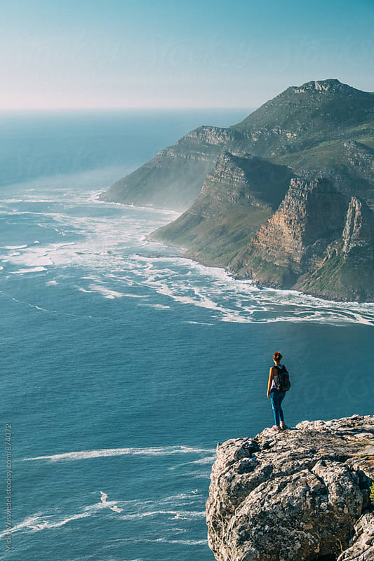 Hiker on a rocky outcrop overlooking an expansive scenic sea view by Micky Wiswedel for Stocksy United