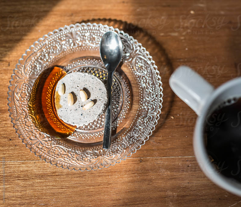 Coffee beside dessert on glass plate and shadow of sunlight by Lawren Lu for Stocksy United