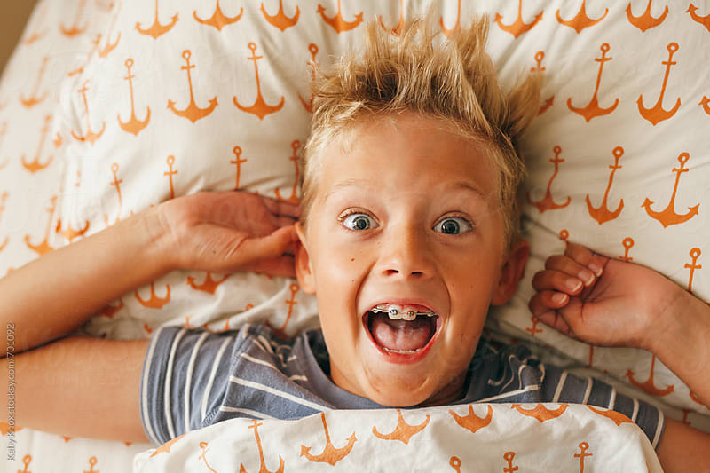 excited boy wakes up in the morning  by Kelly Knox for Stocksy United