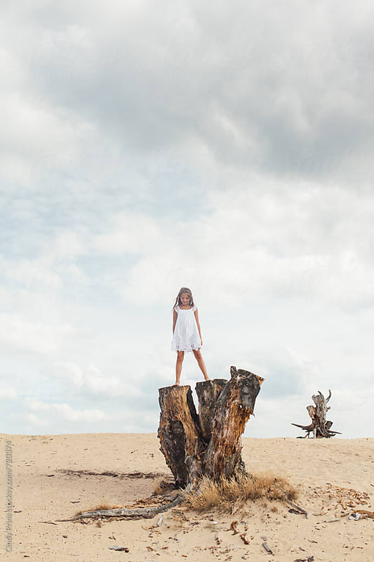Little girl in a white dress standing on a tree trunk in the dunes by Cindy Prins for Stocksy United