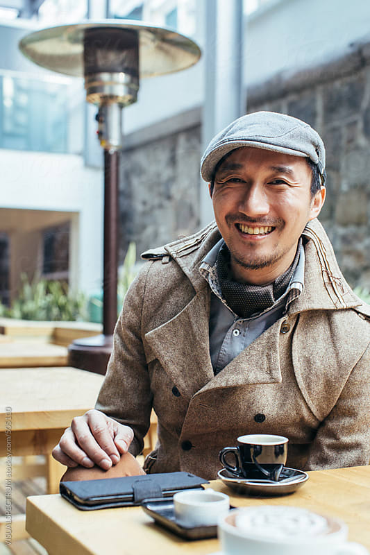 Well-Dressed Smiling Asian Man Sitting on Restaurant Terrace by VISUALSPECTRUM for Stocksy United