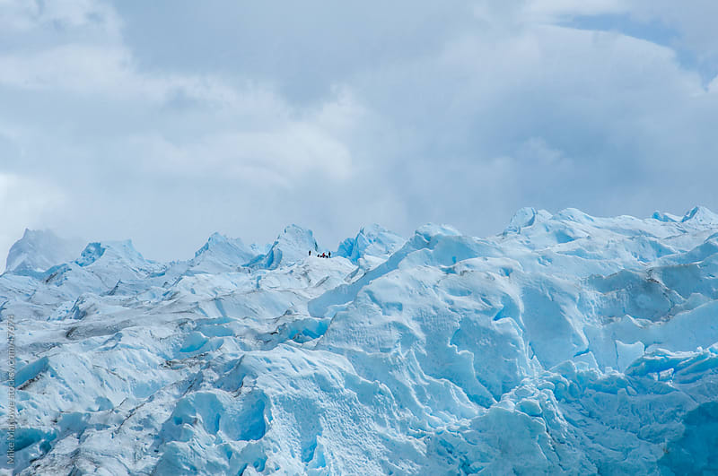 A huge ice glacier with people in the far distance by Mike Marlowe for Stocksy United