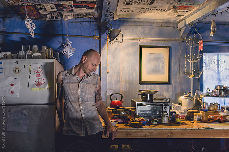 A tattooed artist in his ramshackle home. by Rachel Bellinsky for Stocksy United