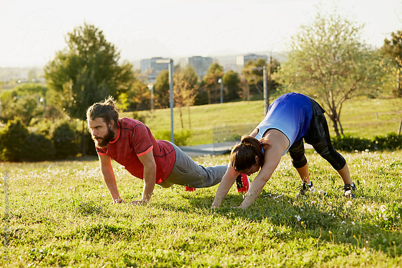 Determined Friends Doing Push-Ups In Park by ALTO IMAGES for Stocksy United