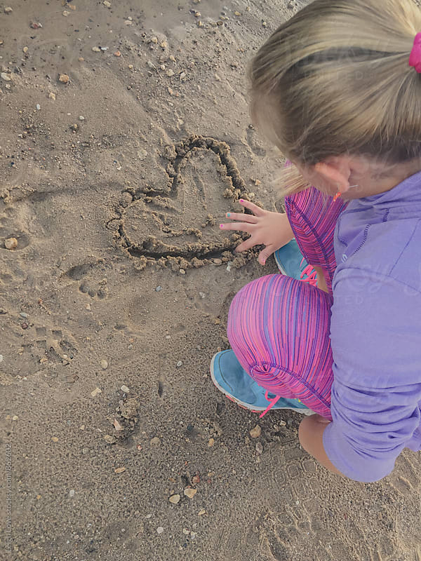 Young Girl With Blonde Hair Draws A Heart In Sand by Leigh Love for Stocksy United