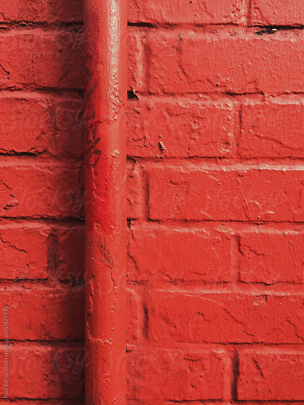 Painted red wall and gutter pipe, close up by Paul Edmondson for Stocksy United