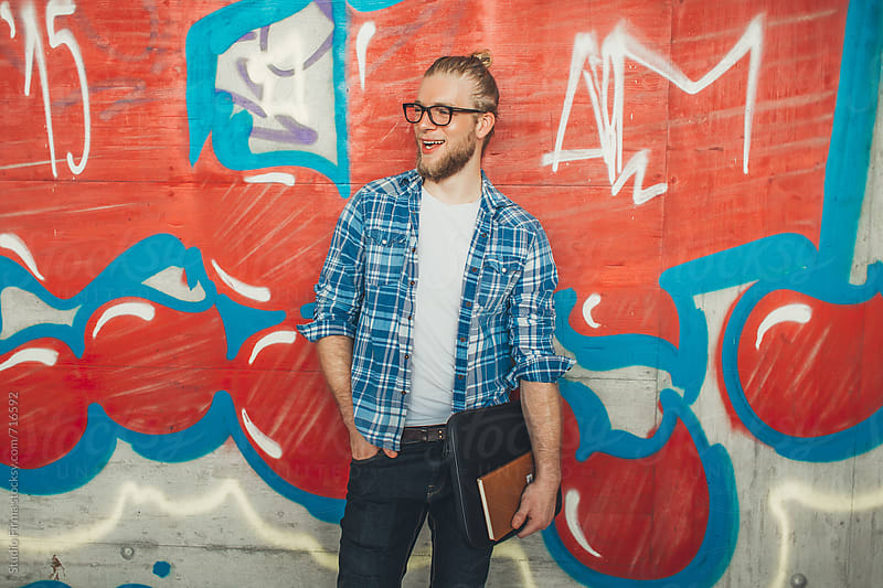 Smiling young man standing against colorful graffiti wall. by Studio Firma for Stocksy United