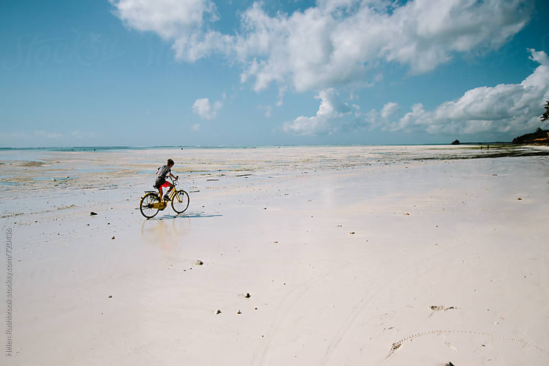 Teenage boy riding a bicycle along a beach at low tide by Helen Rushbrook for Stocksy United