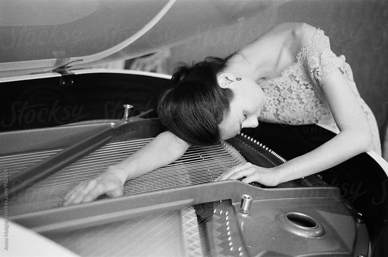 A black and white film portrait of a young beautiful woman lying on a piano by Anna Malgina for Stocksy United