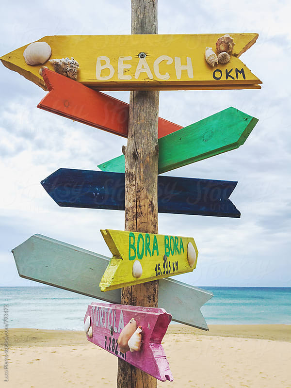 Wooden post with many written signs of different destinations in all directions by Luca Pierro for Stocksy United
