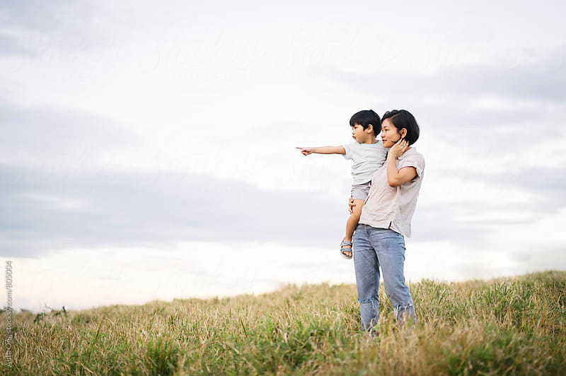 Mother and son together at grass field by Alita Ong for Stocksy United