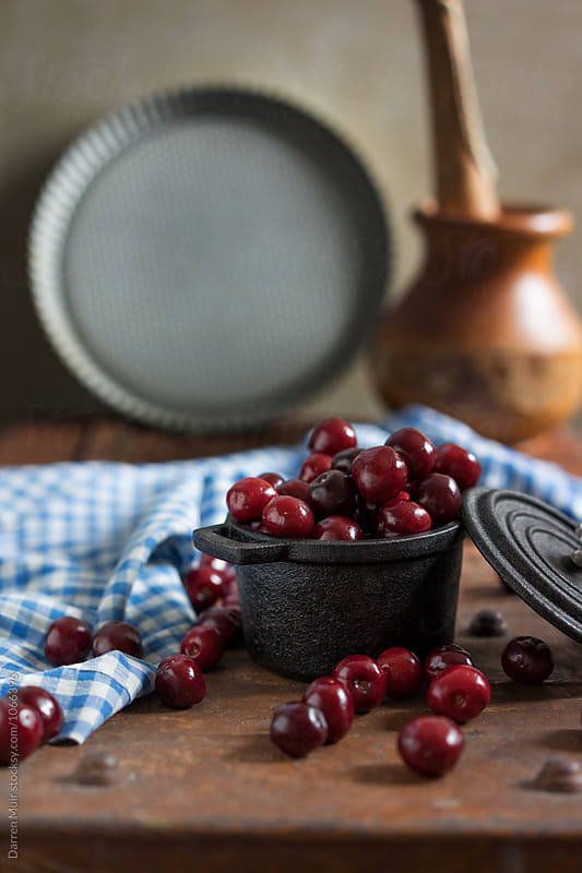 Cherries in a small cast iron pot ready to be prepared for a recipe. by Darren Muir for Stocksy United