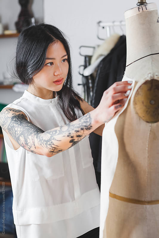 Fashion Designer with Tattooed Arm Working on a Mannequin by Giorgio Magini for Stocksy United