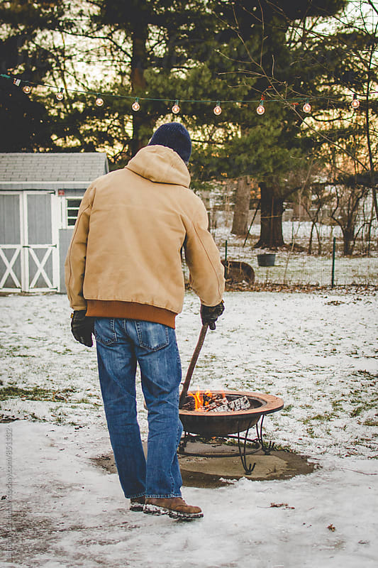 Man using stick to poke fire pit outdoors in winter by Lindsay Crandall for Stocksy United
