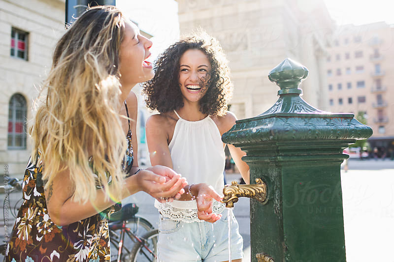 Girls having fun together in the city in summer  by michela ravasio for Stocksy United