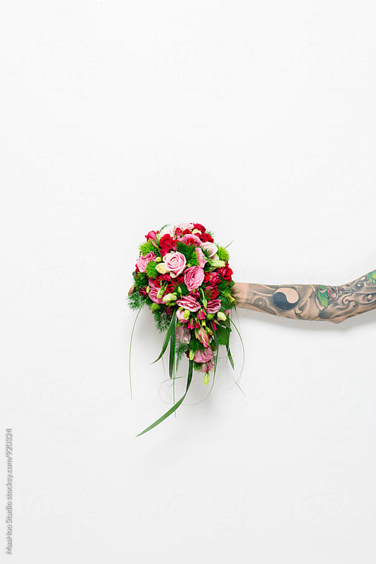 Hand with tattoo holding a bunch of flower by MaaHoo Studio for Stocksy United