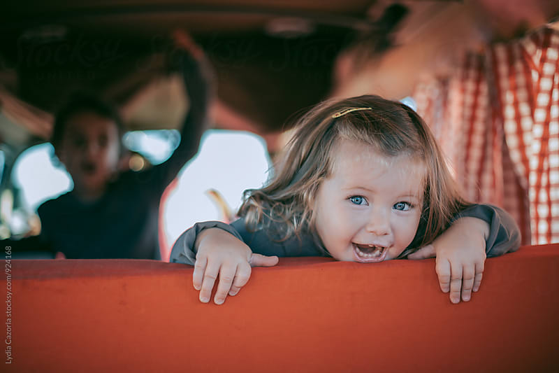 Little girl looking thru the seat of a camper van by Lydia Cazorla for Stocksy United