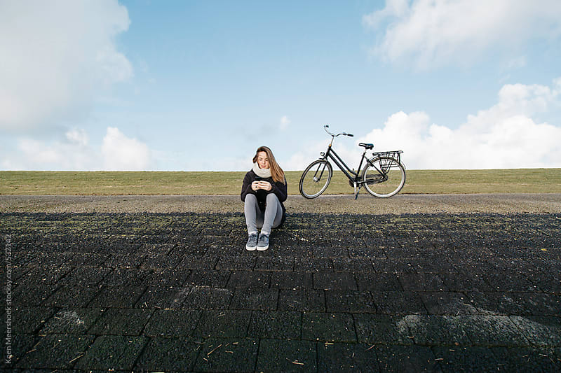 Young woman sits at a dyke and texting with her mobile phone. by Koen Meershoek for Stocksy United