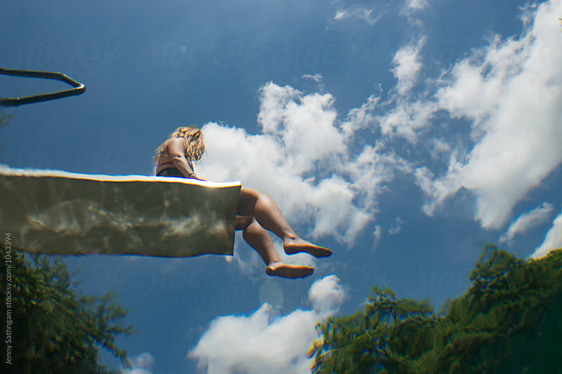 Woman dangling legs off diving board by Jenny Sathngam for Stocksy United