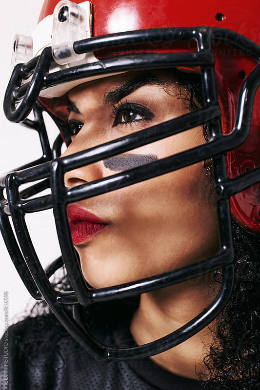 Closeup portrait of a woman wearing a red football helmet. by BONNINSTUDIO for Stocksy United