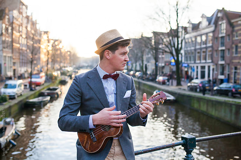 Young man standing on a bridge playing a ukelele by Ivo de Bruijn for Stocksy United