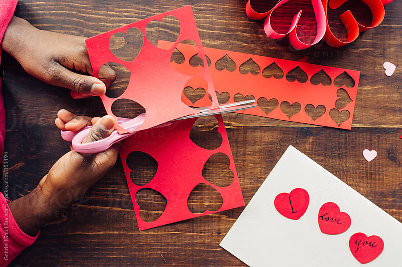 Black girl's hands cutting valentines by Gabriel (Gabi) Bucataru for Stocksy United