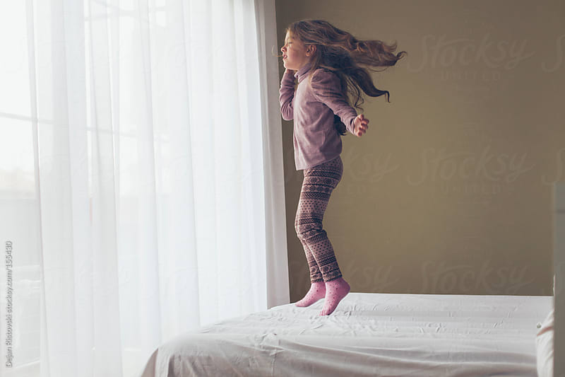 Girl jumping on the bed by Dejan Ristovski for Stocksy United