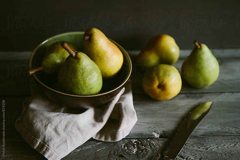 Pears in a bowl on a table by Helen Rushbrook for Stocksy United