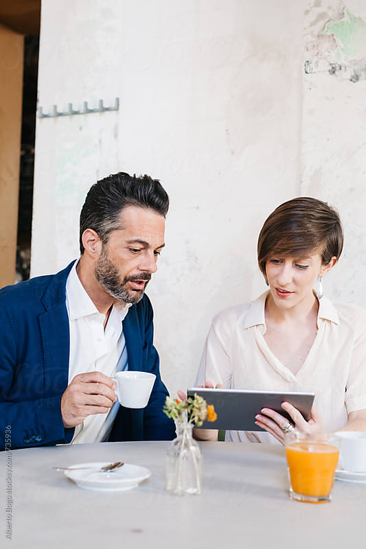 Two colleagues sitting in a cafe with tablet by Alberto Bogo for Stocksy United
