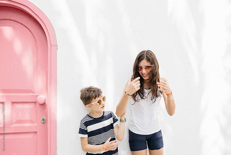 Two kids' funny moment in front of a white wall with a pink door by Beatrix Boros for Stocksy United