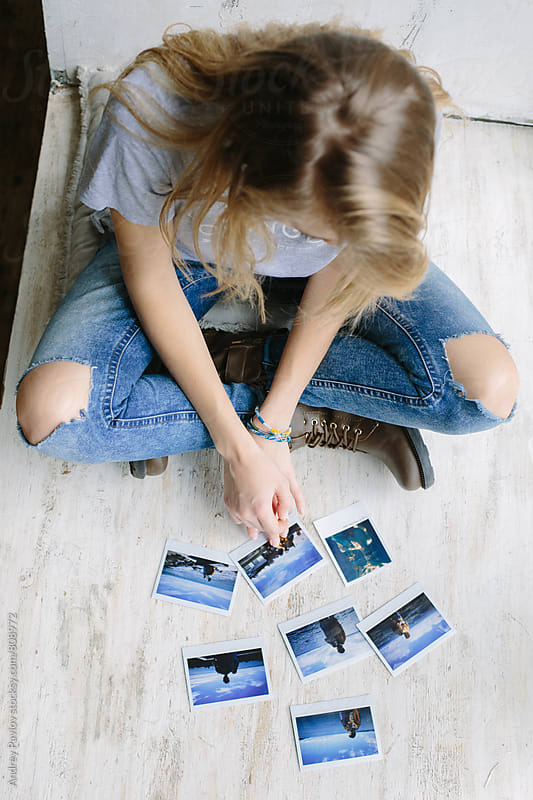 Overhead photo of young blonde woman looking at old snapshots by Andrey Pavlov for Stocksy United