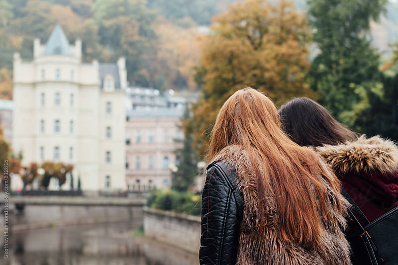 Friends Pausing by Riverside in Karlovy Vary by Geoffrey Hammond for Stocksy United