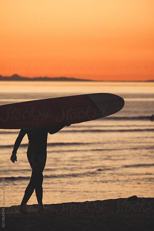 Surfer silhouetted against a warm orange sunset in California. by RZ CREATIVE for Stocksy United