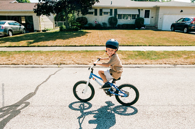 boy rides two wheeler in the street by Maria Manco for Stocksy United