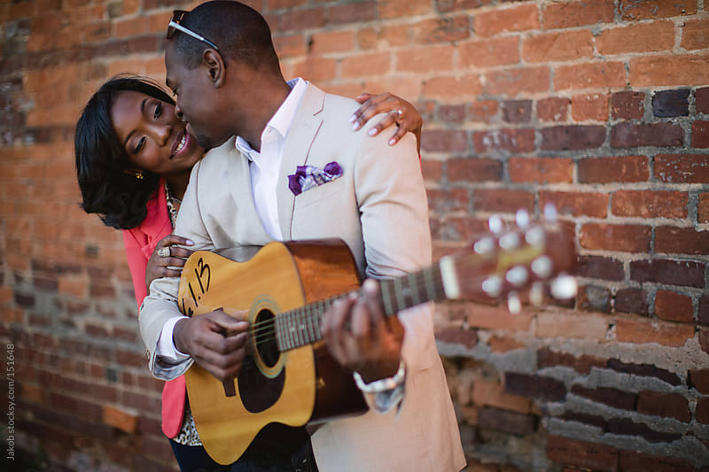 A beautiful african-americancouple outside with a guitar by Jakob for Stocksy United