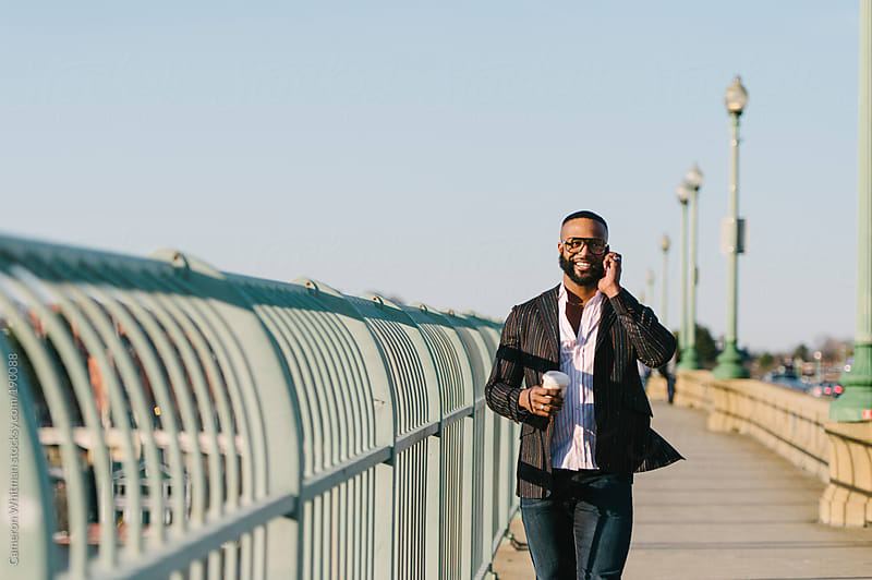Man talking on phone walking along Key Bridge, Washington DC by Cameron Whitman for Stocksy United