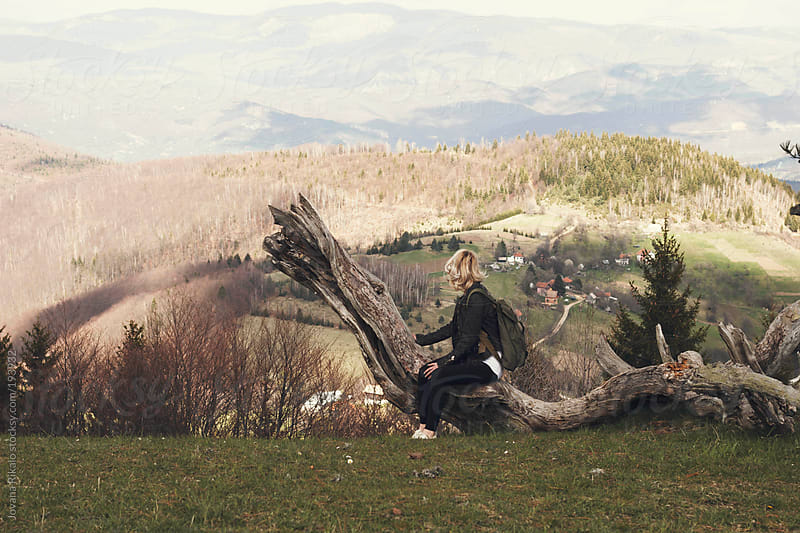 Young woman sitting on a big branch and enjoy the view by Jovana Rikalo for Stocksy United