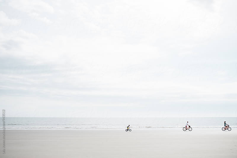 3 kids riding their bikes on the beach by Léa Jones for Stocksy United