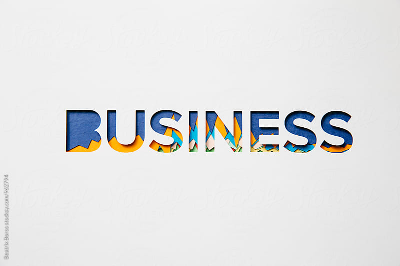 Business letters cut out of cardboard with graphs in the background by Beatrix Boros for Stocksy United