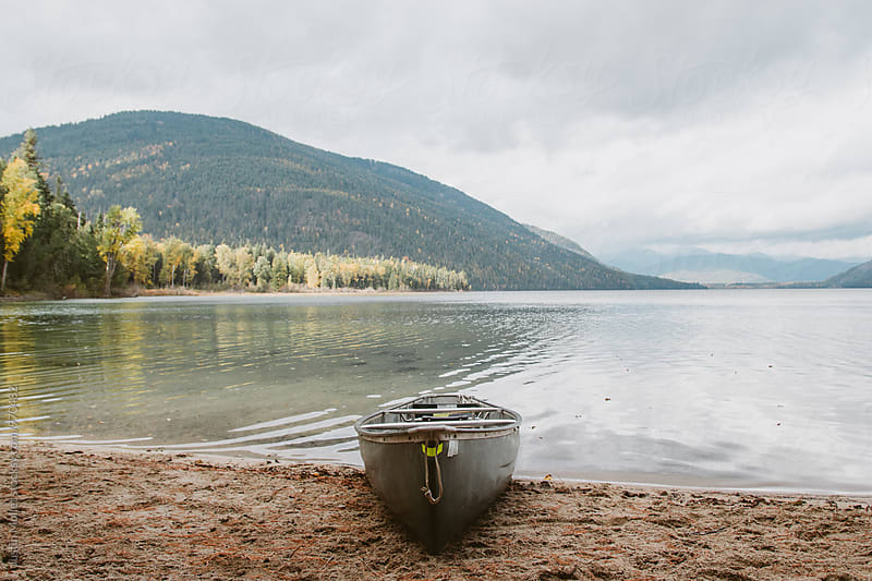 Canoe resting on the beach by Justin Mullet for Stocksy United