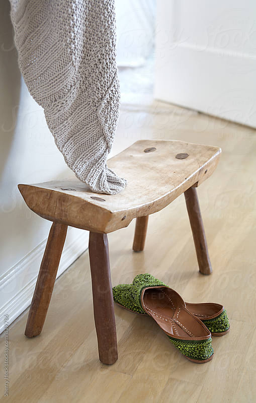 Handcrafted stool in entryway with green slippers and hanging white blanket by Sherry Heck for Stocksy United