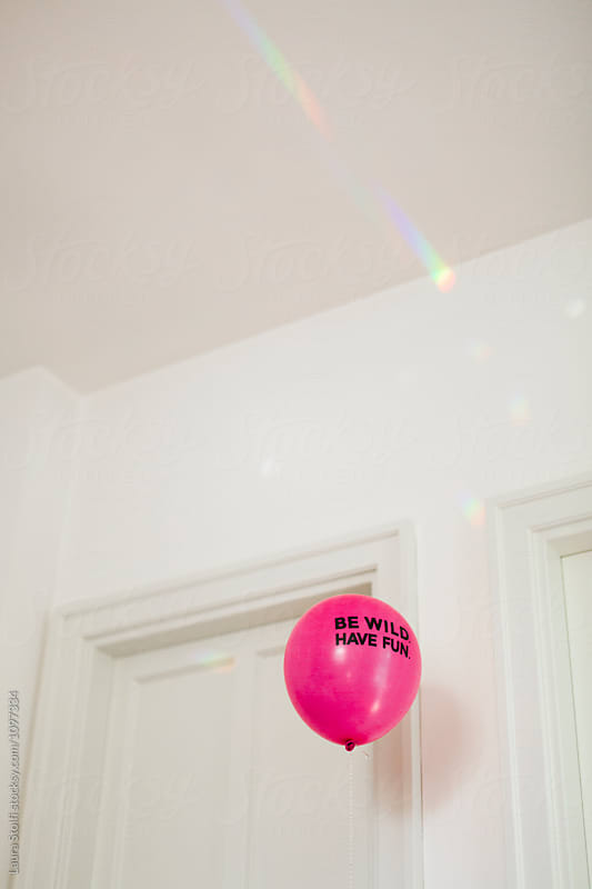 Pink balloon with cool message on it & rainbow by Laura Stolfi for Stocksy United