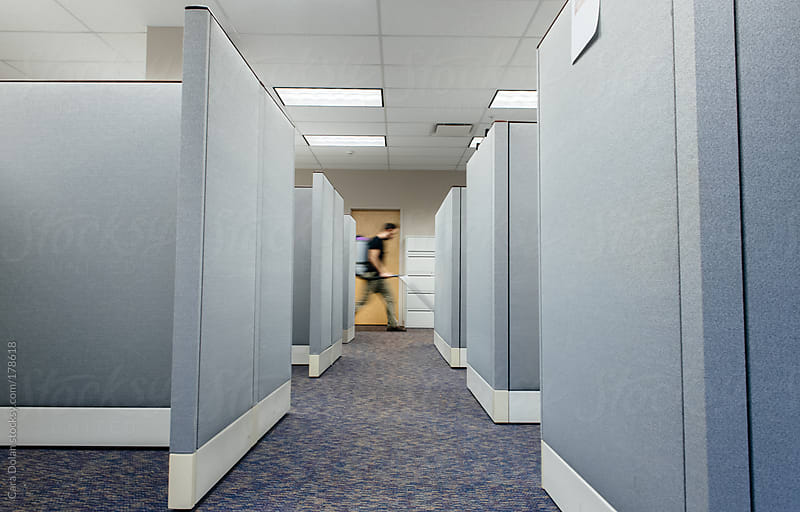 Janitor walks by office cubicle area with vacuum cleaner on his back by Cara Dolan for Stocksy United