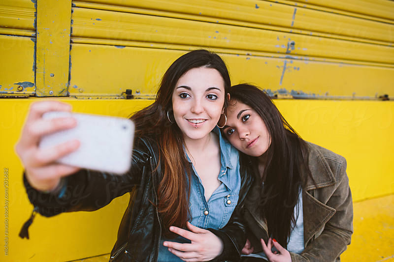 Female friends taking a selfie by michela ravasio for Stocksy United