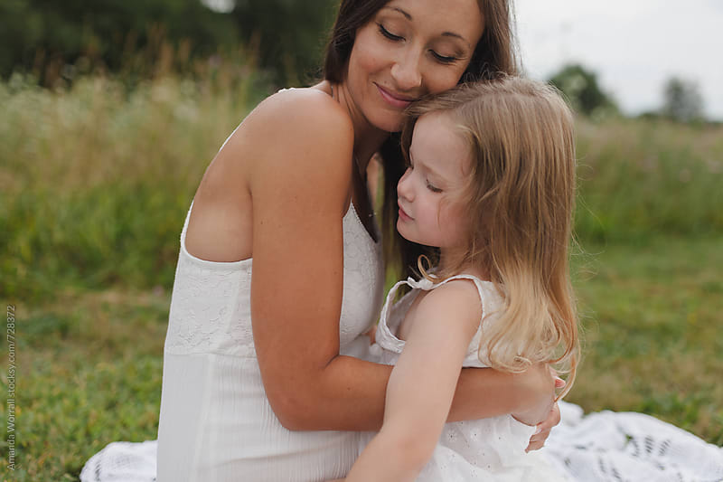 Mother and daughter hugging outdoors by Amanda Worrall for Stocksy United