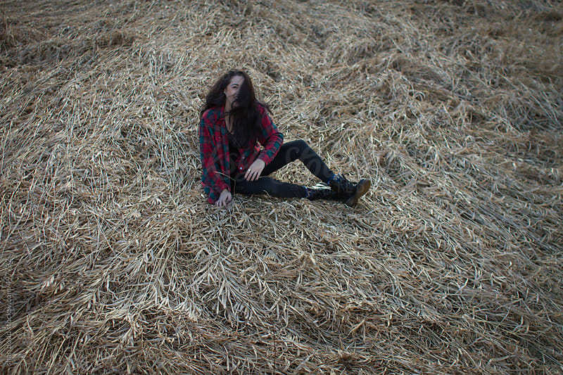 laying down in a grassy field  by shan dodd for Stocksy United