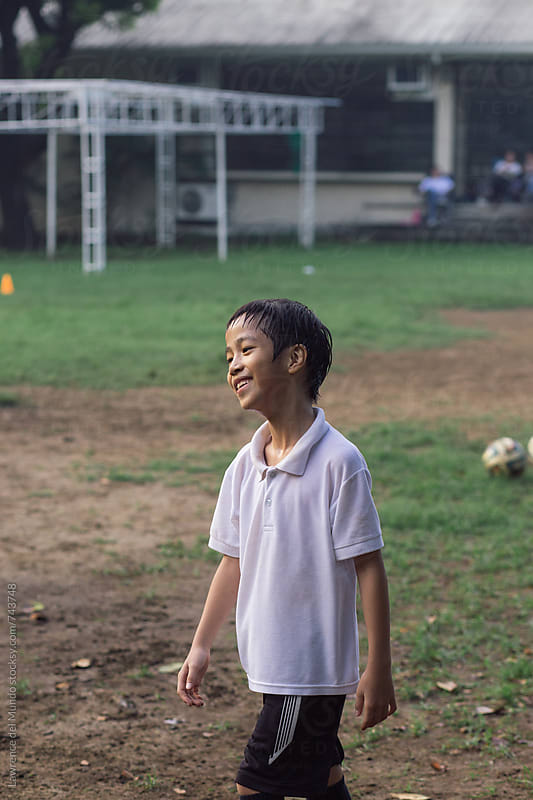 Portrait of young football player enjoying himself at the games by Lawrence del Mundo for Stocksy United