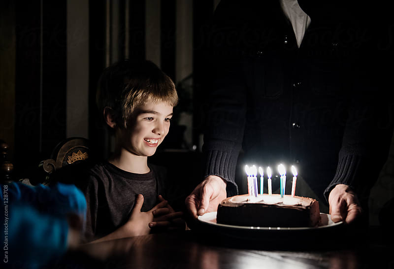 Boy is just about the blow out the candles on his birthday cake by Cara Dolan for Stocksy United